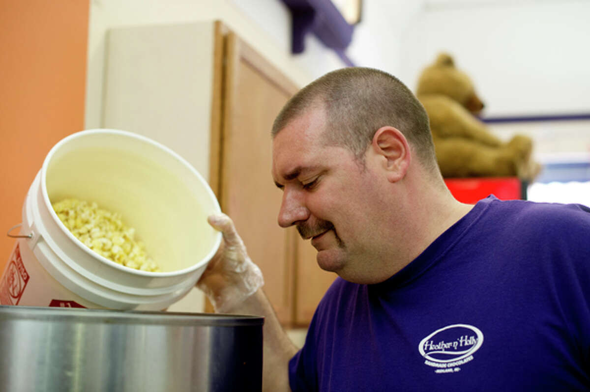 Roger Bebeau Jr. watches the caramel mixture before dumping in the popcorn while making caramel corn at Heather 'n Holly at its downtown location in Midland. He said he is careful to ensure that the batches are uniform. The shop sells many different mixes of popcorn.