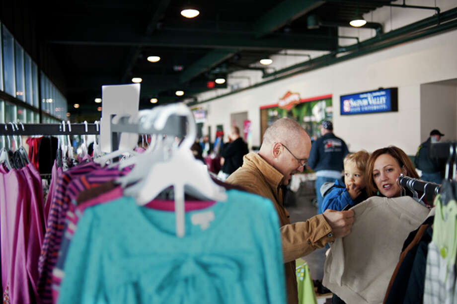 "ZACK WITTMAN | for the Daily News From left, Joe Seka, Sam Seka, 3, and Sarah Seka browse children's clothing at the Deals at the Diamond Indoor Sidewalk Sale at the Dow Diamond on Saturday afternoon. ""This is our first time at the sale,"" Sarah Seka says, ""We just moved here from Philly, actually."""