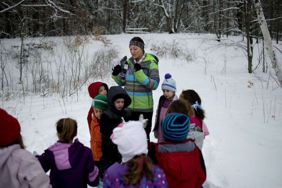 NICK KING | nking@mdn.netStudent teacher Samantha Bralwey, center, gets ready to pass out four birds to kindergartners in a wooded area behind the school for their Nature Kindergarten lesson at Floyd Elementary School. Photo: Nick King/Midland  Daily News