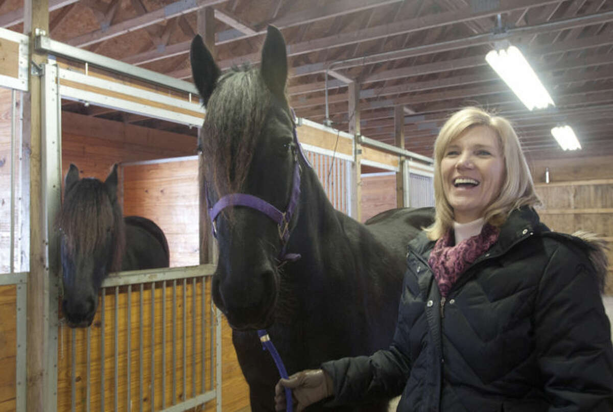 AP Photo | The Saginaw News, Jeff SchrierSandy Bonem holds her horse, Mariska, in her stable in Larkin Township.