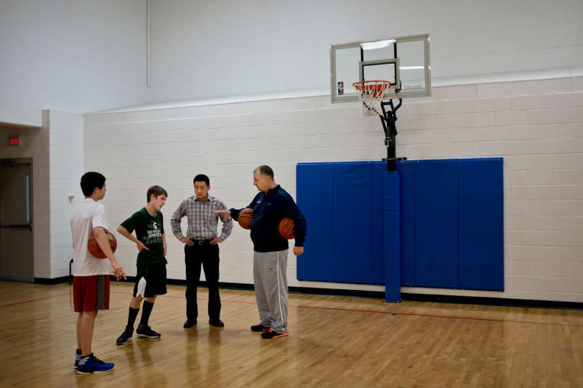 SEAN PROCTOR   sproctor@mdn.netBob Taylor, right, head coach of the Midland Basketball Academy, and T.J. Scheid, who coaches eighth grade at the academy, talk with Jaik Bovee and Joe Fabiano, both 14, at the Midland Community Center. Taylor has been head coach of the program for three years, following stints as head coach for both high school and college basketball teams.