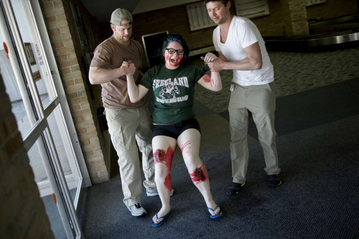 NICK KING | nking@mdn.net Freeland High School student Bailey Marti, 15, center, is helped up by CMU Healthcare Emergency Medicine Residents Stephen McIlmoil, left, and Robert Burge during the Tri-Annual Emergency Exercise Thursday at the old terminal at MBS International Airport.