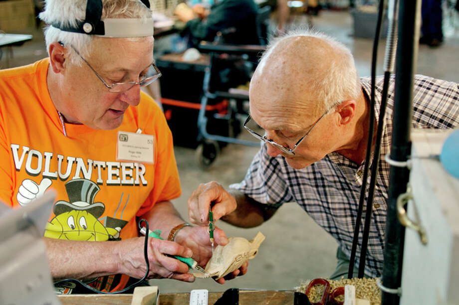 NICK KING | nking@mdn.net Students Wayne Warner, of Galdwin, right, and Roger Wills, Belding, work on carving a meadowlark during the Michigan Wood Carvers Association Seminar at the Midland County Fairgrounds on Wednesday. The two were part of a class on song bird carving by Den Donaghy, of Saginaw. The week long event brings together woodcarvers and professional instructors who teach techniques and classes on specific skills. The seminar, which goes until May 24, is open from 8 a.m. to 4:30 p.m. The classes are only for paying pre-registered students, but the public is welcome, free of charge, to come see the wide variety of wood creations. Photo: Nick King/Midland  Daily News / Midland Daily News