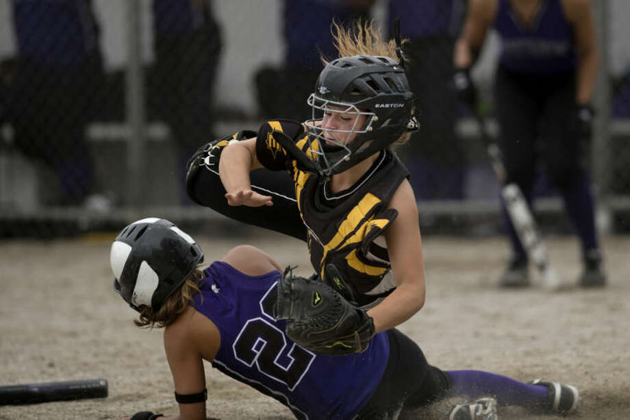 NEIL BLAKE | nblake@mdn.netBullock Creek's Maison Kalina falls over Swan Valley's Sarah Addy as Addy slides safely into home plate during the district game at Bullock Creek High School on Wednesday.