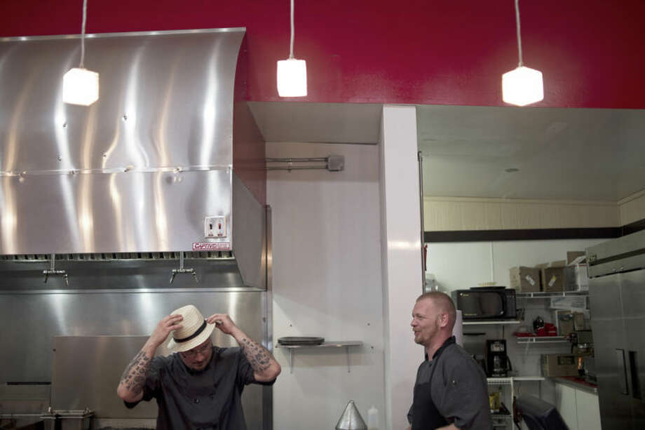 SEAN PROCTOR | sproctor@mdn.netJake Skyme, the kitchen manager at Wiseguys, jokingly puts on a fedora while Dan James, the owner of Wiseguys, looks on and laughs Wednesday afternoon at the new restaurant, located at 405. E. Main St. Photo: Sean Proctor/Midland  Daily News