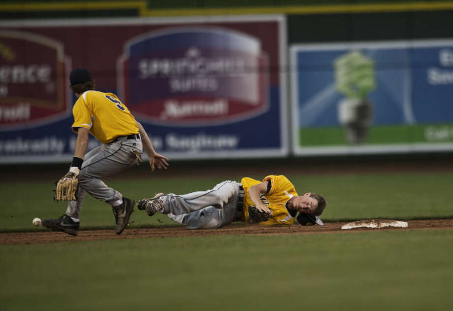 SEAN PROCTOR | sproctor@mdn.netMidland's Tanner Gross falls to the ground after attempting to catch an infield hit by Bullock Creek as teammate Thomas Smith scrambles for the ball Monday evening during their game at Dow Diamond. Photo: Sean Proctor/Midland  Daily News