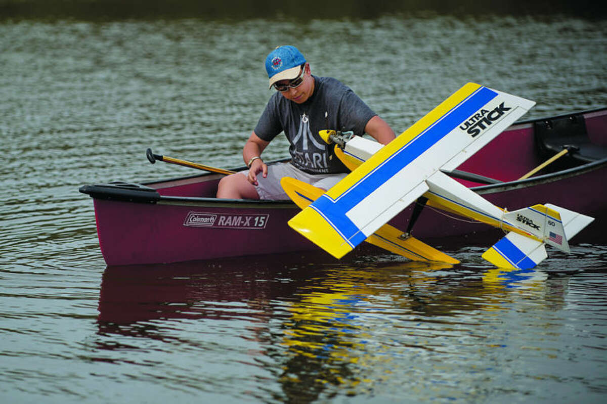 NEIL BLAKE   nblake@mdn.netRyan Hallman, 14, of Breckenridge, pulls a remote controlled plane into a canoe after a successful landing on Kiwassee Lake at Stratford Woods Park on Saturday. Members from Midland RC Modelers Club kept the canoe at hand to recover planes that crashed or were stranded in the lake during their Float Fly event.