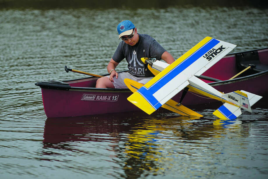NEIL BLAKE | nblake@mdn.netRyan Hallman, 14, of Breckenridge, pulls a remote controlled plane into a canoe after a successful landing on Kiwassee Lake at Stratford Woods Park on Saturday. Members from Midland RC Modelers Club kept the canoe at hand to recover planes that crashed or were stranded in the lake during their Float Fly event. Photo: Neil Blake/Midland  Daily News