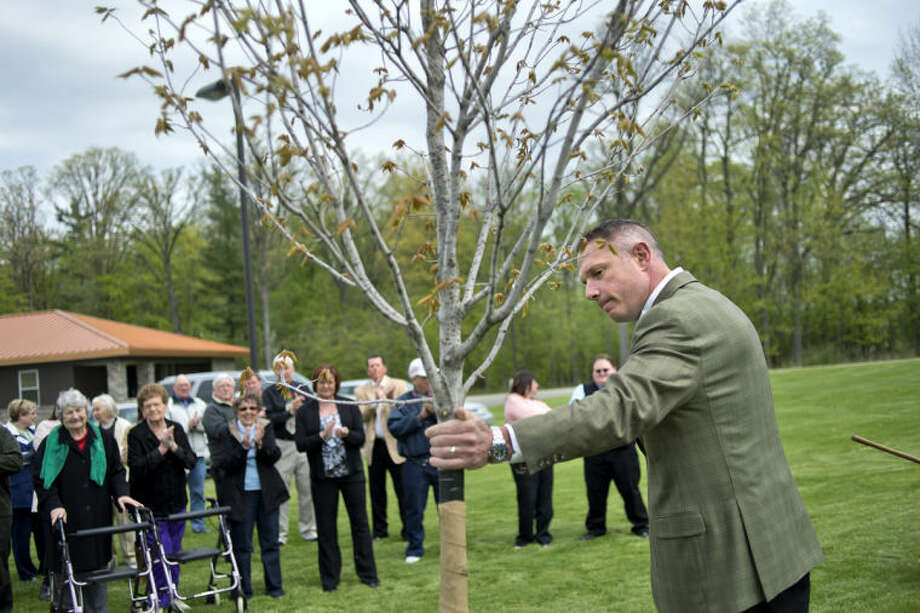 NICK KING | nking@mdn.netMidland County Commission Chairman Mark Bone admires a maple tree that was dedicated in honor of Howard Schoenherr Tuesday at Pinecrest Farms in Midland. In addition to the tree, a bench will be installed at the site. About 30 people attended the event for Schoenherr, who died in September. Photo: Nick King/Midland  Daily News