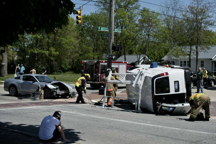 SEAN PROCTOR | sproctor@mdn.net Firefighters work on cleaning the scene after a van flipped over after being struck by another car at the corner of Ashman and Buttles on Thursday afternoon. Photo: Sean Proctor