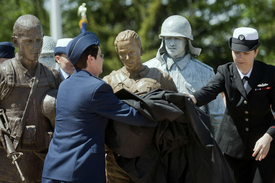 NICK KING | nking@mdn.netAir Force Lt. Col. Anne Dutcher, left, and Navy Petty Officer 2nd Class Nicole Beson, right, unveil the female soldier statue at the Coleman Veterans Memorial during a Memorial Day and dedication ceremony on Monday. Photo: Nick King/Midland  Daily News