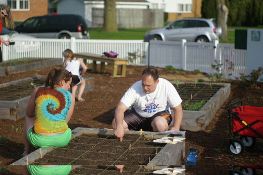 Amber and Ron Huber work in the Community Garden. Photo supplied