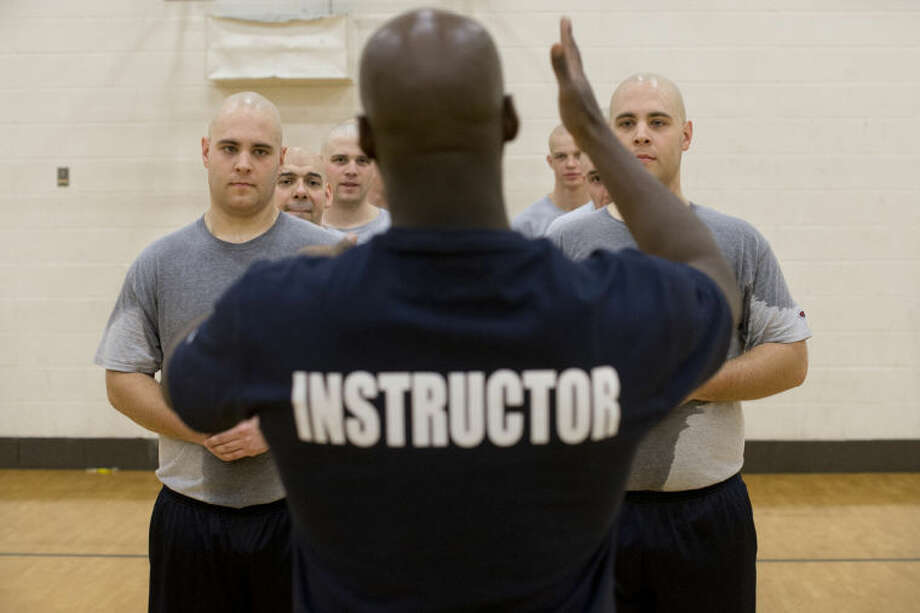 NEIL BLAKE | nblake@mdn.netAlex Jobes, left, and Anthony Jobes listen to an instructor during physical training on Feb 21. Physical training took place each morning before class five days a week. If recruits failed to meet the physical requirements they were dropped from the program. Photo: Neil Blake/Midland  Daily News