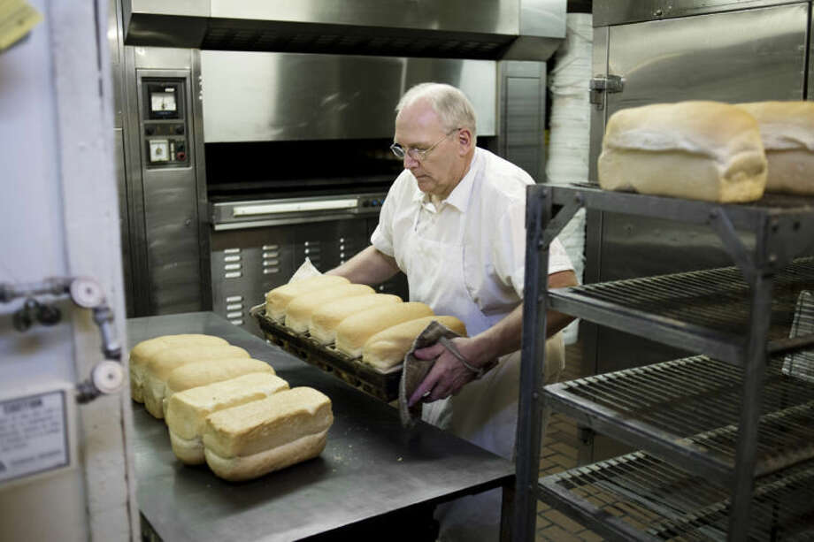 "NEIL BLAKE | nblake@mdn.netHamilton pastries co-owner Matthew Hamilton pulls freshly baked bread from the oven. Hamilton started worked at the business for his father, Raymond Hamilton, as a 16-year-old for spending money. ""You have to time it right because everything cooks at a different temperature,"" Matthew said about the oven. ""The donuts go in first because they have to be ready first thing (when the store opens)."" Photo: Neil Blake/Midland  Daily News"