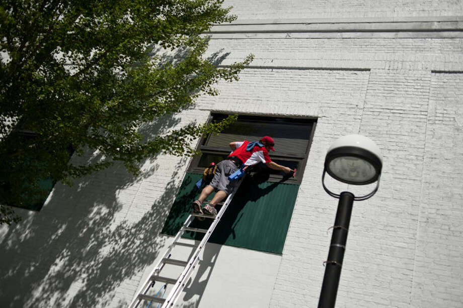 SEAN PROCTOR | sproctor@mdn.netMark Haskin, of Shine Window Care, washes windows in downtown Midland on Wednesday afternoon. Haskin said that after lunch he planned to ask various downtown businesses if they were interested in having their windows cleaned. Photo: Sean Proctor
