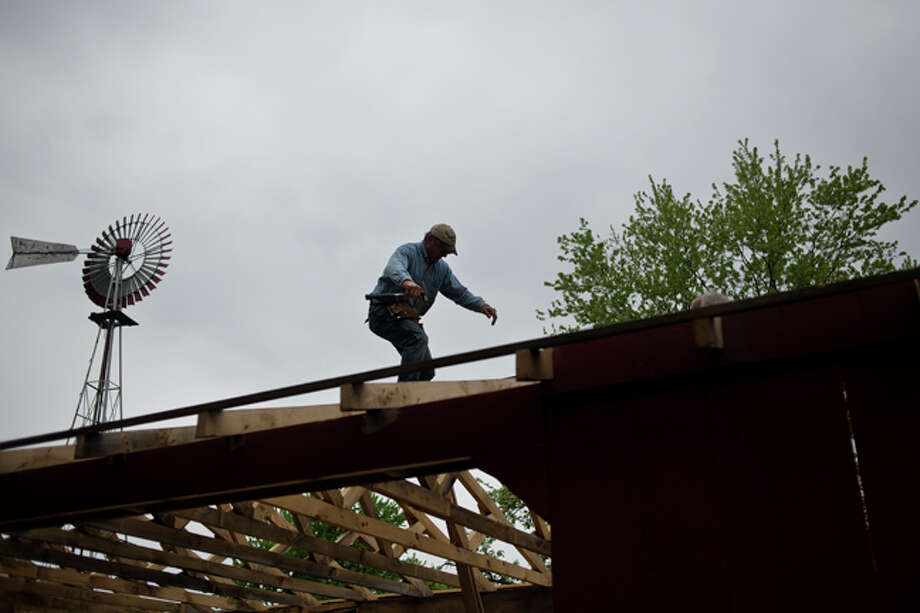 SEAN PROCTOR | sproctor@mdn.net Chuck Dinsmore, president of the Sanford Historical Society, walks on the rafters while building the new Sanford Museum pavilion on Friday afternoon. The pavilion will house farming equipment and a carpentry shop display, Photo: Sean Proctor/Midland  Daily News / Midland Daily News