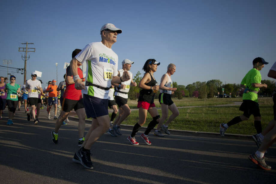 NEIL BLAKE | nblake@mdn.netRunners, including Eugene Barry of Clawson, center, begin the Great Lakes Bay Marathon on Sunday at Dow Diamond. The race started and ended at the stadium.