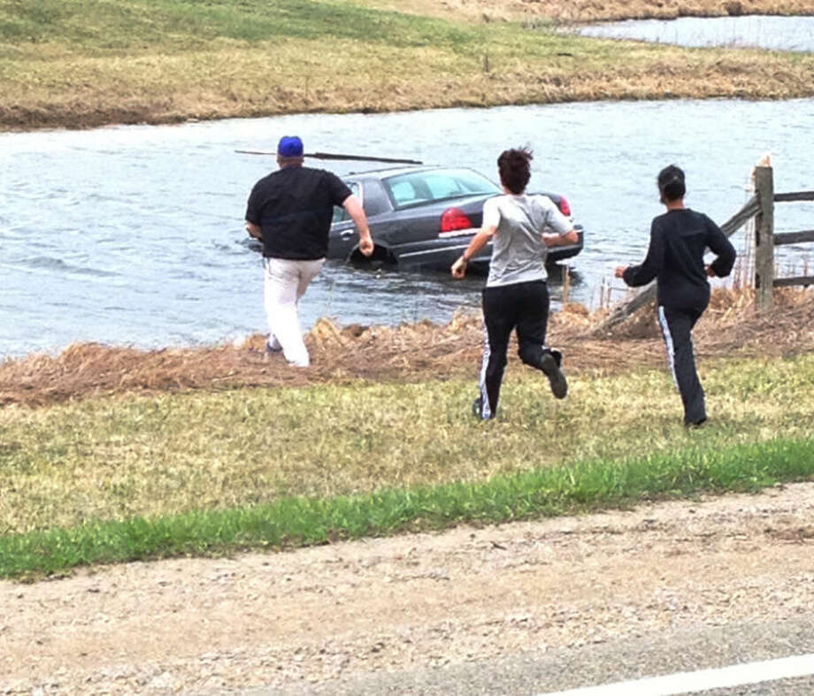Photo providedFrom left, Coleman coaches Tom Pashak, Katherine Benchley and Keisha Acker rush toward a car in a pond to rescue the driver after he veered off the road on M-66 near McBain on Tuesday afternoon.