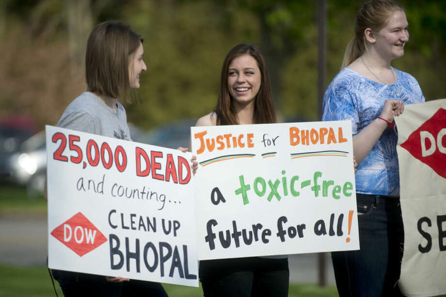 NEIL BLAKE   nblake@mdn.netConcordia College alumnae Caitlyn Schuchhardt, left, and Megan John stand next to Catherine Miller, a current Condcoria College student, while holding signs outside of the Midland Center For the Arts on Thursday morning during The Dow Chemical Co.'s annual stockholders meeting. Photo: Neil Blake/Midland  Daily News