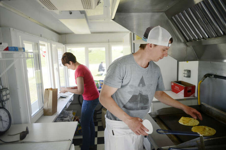 NEIL BLAKE | nblake@mdn.netAmber and Jake Wendt, of Midland, prepare a lunch in their mobile restaurant, The Crave Cave, on Wednesday. The restaurant is open from 11 a.m. to 2 p.m. Wednesday through Friday and is currently located near the corner of East Pine Street and Third Street. The restaurant opened last week.