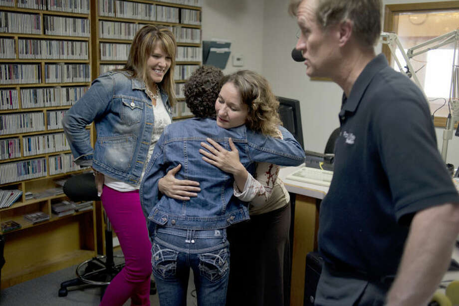 "NEIL BLAKE | nblake@mdn.netRadio host Shannyn Caldwell hugs Mary Juengel, 13, as Sarah Schieber, right, looks on and radio host Peter Brooks talks with Marni Juengel (not pictured) at Family Life Radio in Midland on Wednesday. Schieber and Juengel were interviewed by Caldwell and Brooks about their upcoming concert performance at the Christian Celebration Center on Saturday at 7 p.m. Juengel is currently battling leukemia and recently released a recording of her song, ""Through my Scars,"" with the help of Schieber. Photo: Neil Blake/Midland  Daily News"