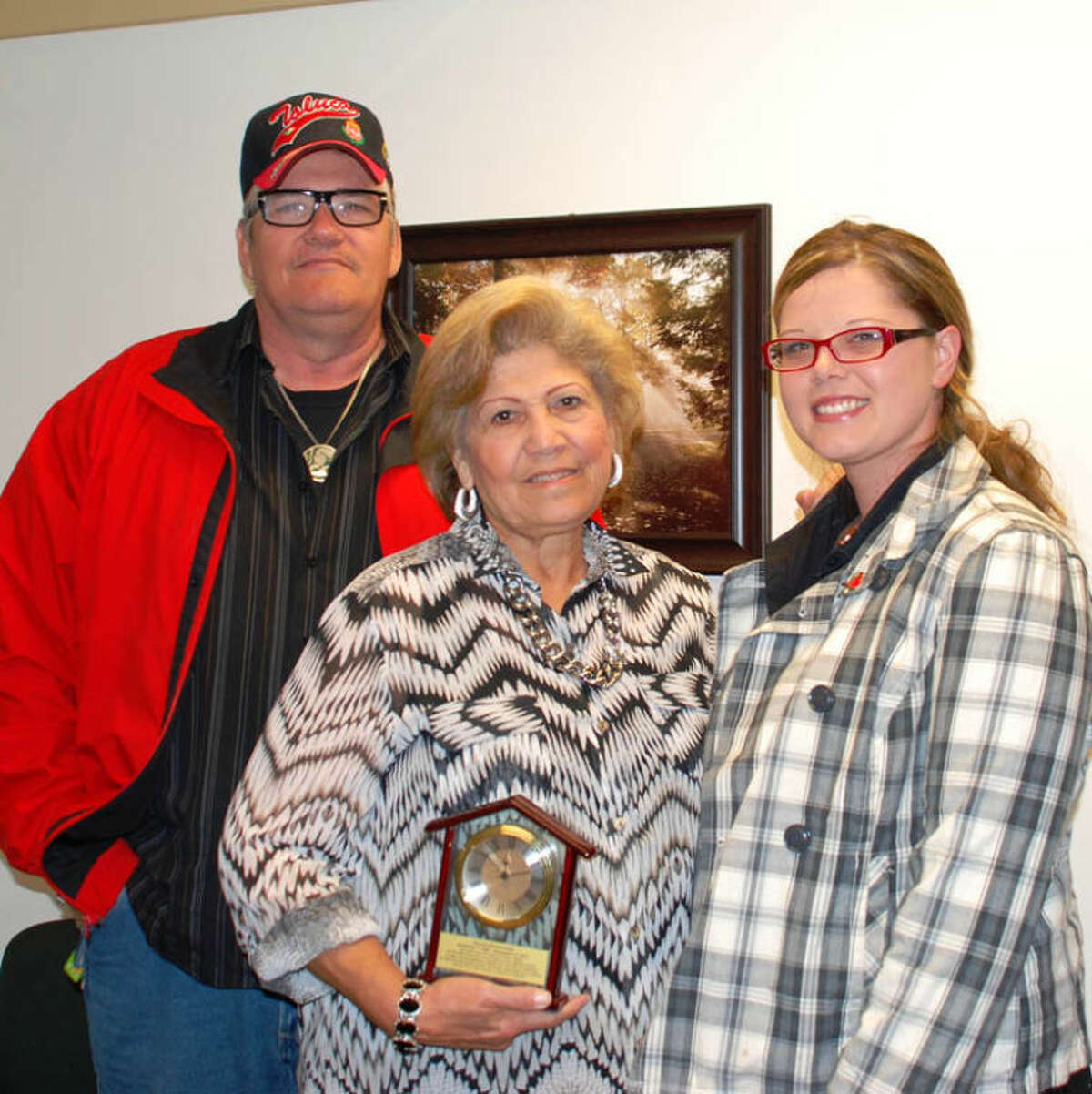 Photo providedGail and Rachel Locke, who serve as foster parents for the Midland County Probate Court, pose with an award they received for their years of service and Kelly Muscott, one of the kids they fostered. Muscott is in the process of becoming licensed to foster.