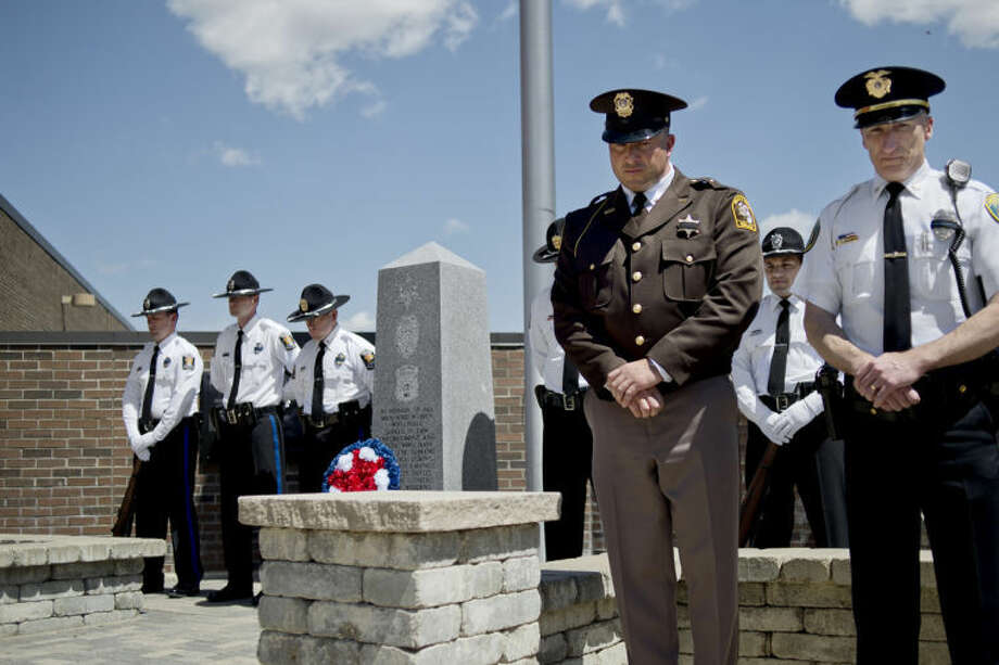 NICK KING | nking@mdn.netMidland County Sheriff Scott Stephenson, left, and Midland Police Chief Cliff Block observe a moment of silence during a ceremony commemorating Peace Officers Memorial Day Wednesday at the Midland Law Enforcement Center. Stephenson and Block placed a wreath at the memorial earlier in the ceremony. The Midland Police Honor Guard stands in the background. Photo: Nick King/Midland  Daily News
