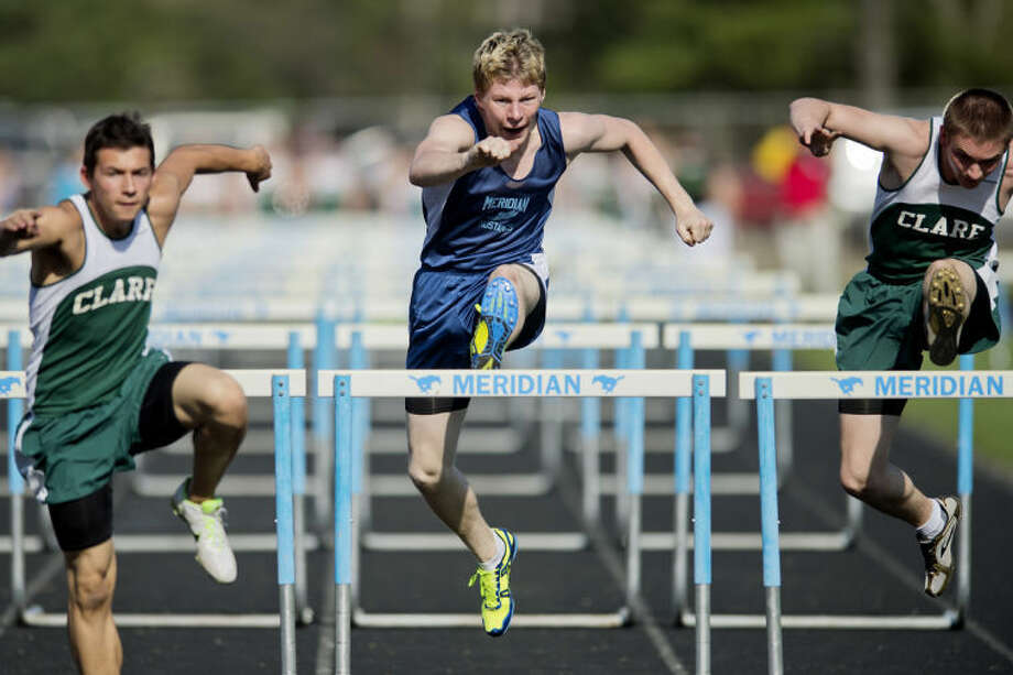 NICK KING | nking@mdn.netMeridian's Seger Jackson, center, clears the last hurdle while competing in the 110 meter hurdles event Wednesday during the Mustangs' track meet against Clare at Meridian High School. At left is Clare's Dean Ayers and, at right, Jordan Hales. Photo: Nick King/Midland  Daily News