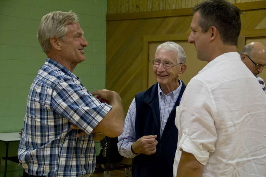 EMILY BROUWER | For the Daily NewsMidland residents Rick Doornbos and Michael DeRuyter, pastor of the Midland Reformed Church, talk to Duane Lehman last week during Lehman's going away party at the church.