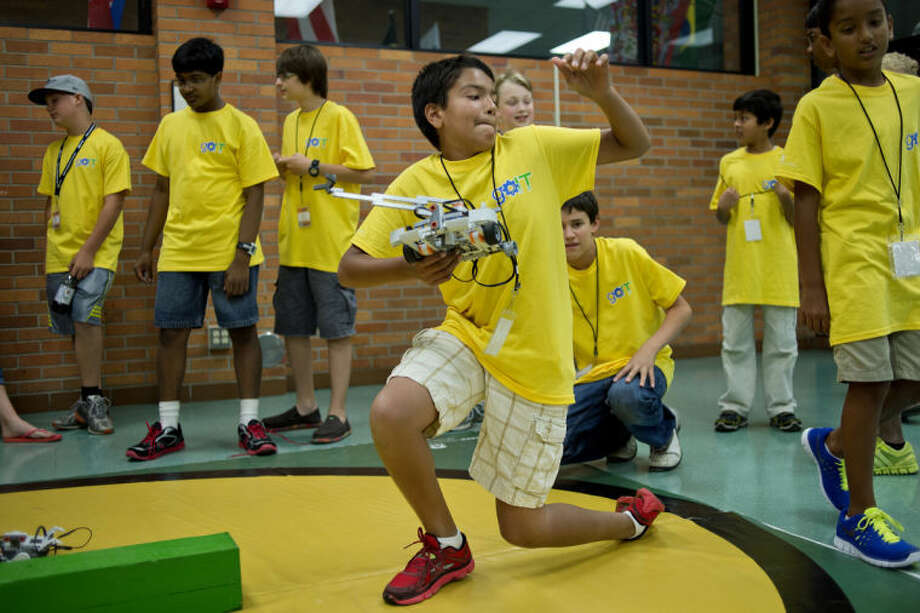 NICK KING | nking@mdn.netAdi Middha picks up his team's robot after a practice run around the course during the Tata Consultancy Services' goIT summer camp Friday at Jefferson Middle School. About 60 students participated in the camp where teams built and programmed robots to travel around a oval track. Photo: Nick King/Midland  Daily News