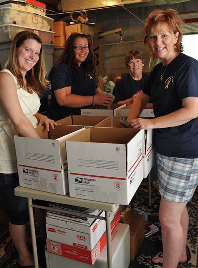 Photo providedAaron's Gifts from Home volunteers, from left, Morgan Birnbaum, Jamie Rozell, Connie Glave and Lori Upleger, fill care packages to send overseas to U.S. military personnel.