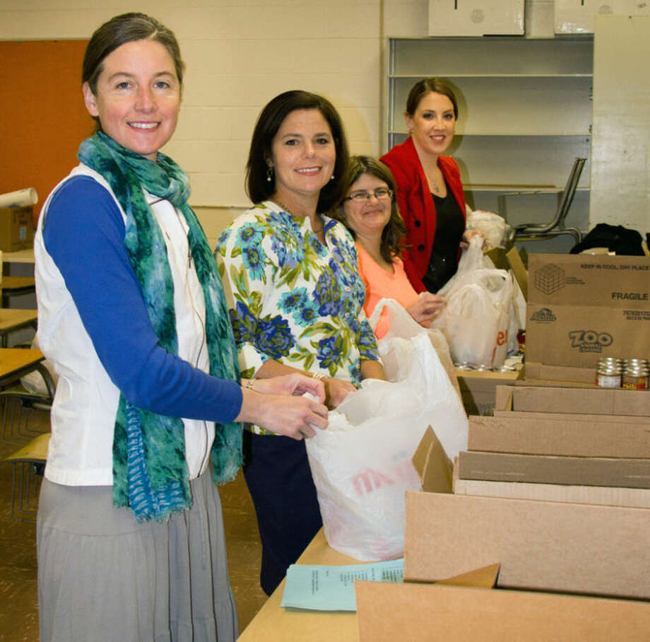Photo providedBackpack Buddies volunteers Deb Ahn, Susan Hammer, Lisa Burton and Mackenzie Kastl fill bags with weekend food for Siebert Elementary students.