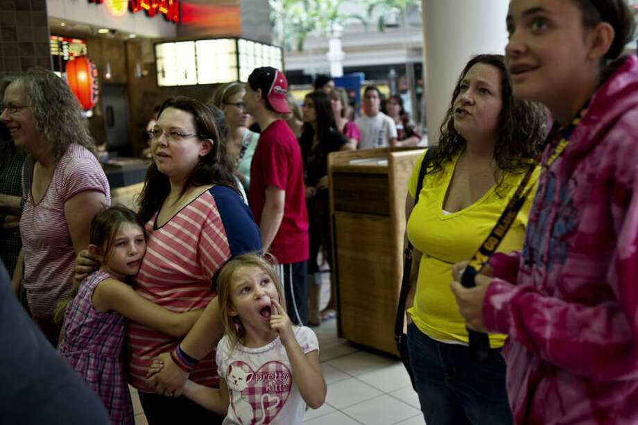 SEAN PROCTOR | sproctor@mdn.net Jeannie Mock, of Sanford, holds on to her children Allie, 7, left, and Meghan, 5, while waiting in line with her mother, Connie Skutt, also of Sanford, for the grand opening of Chip -n- Wich Monday afternoon at the Midland Mall. Mock, who ordered the Firecracker Corned Beef sandwich said she thought it was delicious and plans on coming back with her husband. Photo: Sean Proctor/Midland  Daily News