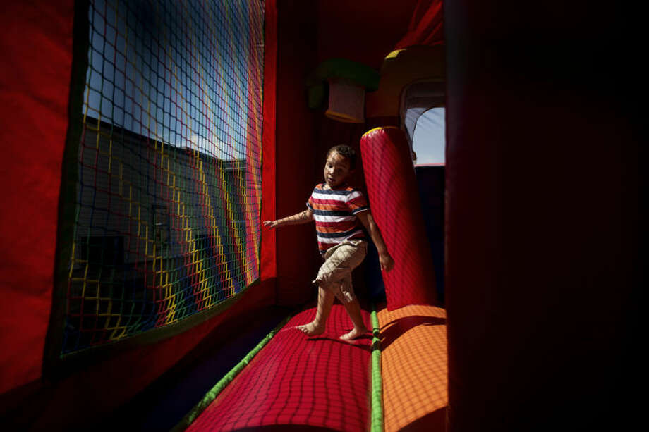 NEIL BLAKE | nblake@mdn.netTyler McGee, 8, plays in the bounce house during the Health and Safety Fair at the Railway Family Center on Saturday. McGee's mother, Sabrina McGee, was working at the Michigan State University Extension Office's booth at the fair. The fair had children's activities while providing information about community services. Photo: Neil Blake/Midland  Daily News