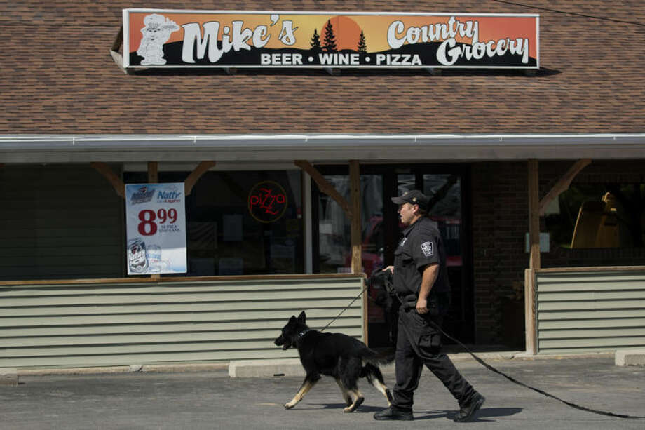 NEIL BLAKE | nblake@mdn.net An officer from the Saginaw Chippewa Tribal Police walks in front of Mike's Country Grocery after a robbery on Sunday. The K9 unit was called for because the suspect left on foot.