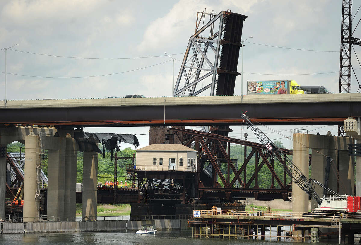 A train makes its way southbound as the northbound section of the Metro-North bridge across the Housatonic River between Stratford and Milford is stuck in the raised position on Thursday, July 2, 2015.