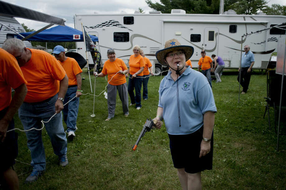 "NEIL BLAKE | nblake@mdn.net Colleen Badour of Essexbille acts as a sheriff as the rest of Chapter V pretends they are a chain gang during the campsite judging during the Gold Wing Road Riders Association's Annual District Convention at the Midland County Fairgrounds. They decorated the campsite with a jail and crime scene for the theme ""Cops and Robbers."" The chapter's saying is ""Chapter V has the most fun."" Photo: Neil Blake/Midland  Daily News"