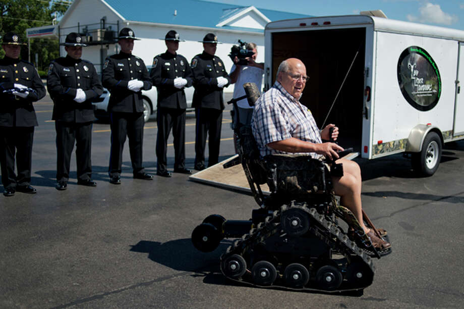 "Nels Larsen, a Midland Vietnam veteran, test drives an all terrain wheelchair that he was surprised with in Auburn on Friday as the Midland Police Honor Guard looks on. The chair was presented by the Police Officers Association of Michigan and was given to recognize Larsen's service and ongoing commitment to honoring other veterans. Larsen runs ""Walleyes for Warriors,"" an organization that hosts veteran's fishing trips. ""Wow,"" Larsen said choked with emotion. ""I don't know what to say."" The chair will give him greater access to the outdoors. Photo: Neil Blake/Midland  Daily News / Midland Daily News"