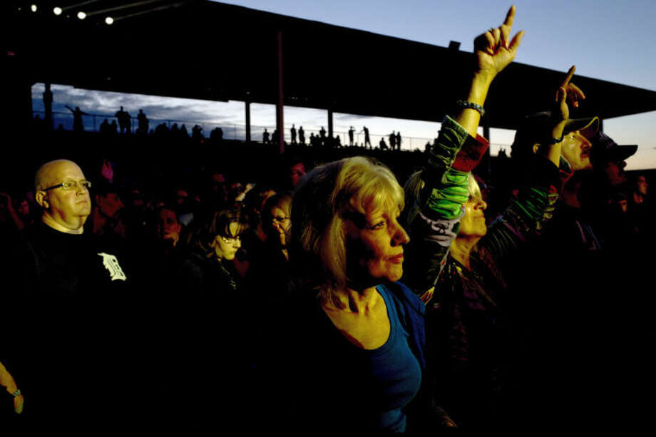 LIBBY MARCH | for the Daily NewsJill Yambrick of Auburn, center, watches quietly as Claudia LaFramboise, center right, throws up her arms during the Lynyrd Skynyrd concert on Sunday at the Midland County Fairgrounds. Photo: Libby March/for The Midland Dail