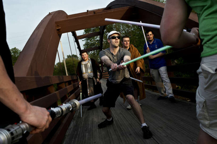 SEAN PROCTOR | sproctor@mdn.netDaniel Rings, center, leads an attack against members of the dark side during a battle on the Tridge in Midland on Sunday, May 19. One side would stand in the middle of the Tridge and attempt to hold their ground while the other group attacked. Photo: Sean Proctor/Midland  Daily News