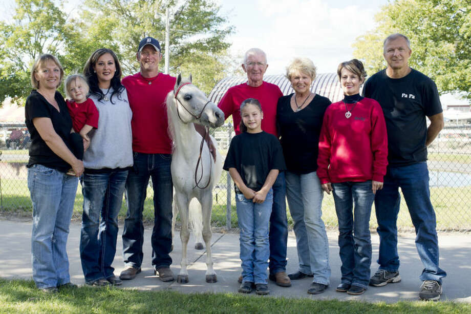 NEIL BLAKE | nblake@mdn.netFrom left, Karie Moody, her daughter, Olivia, 3, Jennifer Westall, Jake Westall, Mike the pony, Nate Root, his wife Kathryn Root, Taylor Westall (in front of Nate), 7, Becky Cook and Gene Cook pose for a photo at the Midland County Fair on Wednesday. Four generations from the family showed ponies in the fair this year.