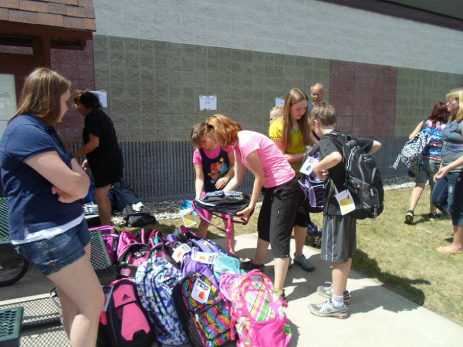 Photo providedYouths check out the variety of backpacks available at the North Midland Family Center's annual summer picnic.