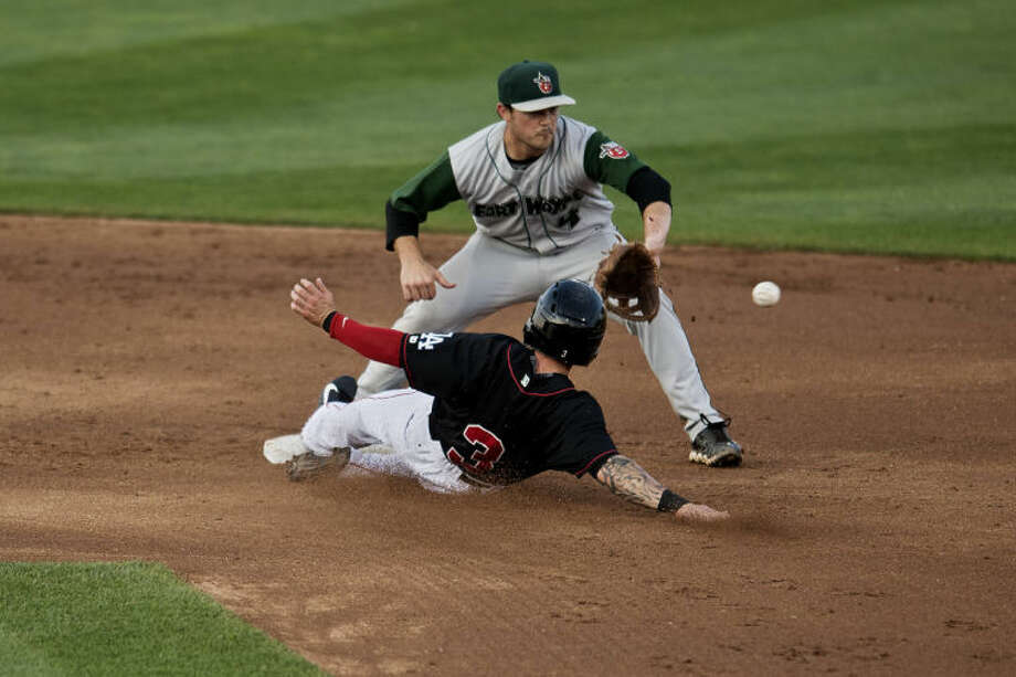 SEAN PROCTOR | sproctor@mdn.netTinCaps infielder Tyler Stubblefield reaches out to catch a ball as the Loons' Robbie Garvey slides into second base Monday at Dow Diamond. Photo: Sean Proctor/Midland Daily News
