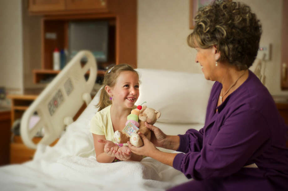 Photo providedRegistered Nurse Kathy Amble comforts Alexis Nader with one of the stuffed animals purchased through funds donated by The Alden and Vada Dow Family Foundations.
