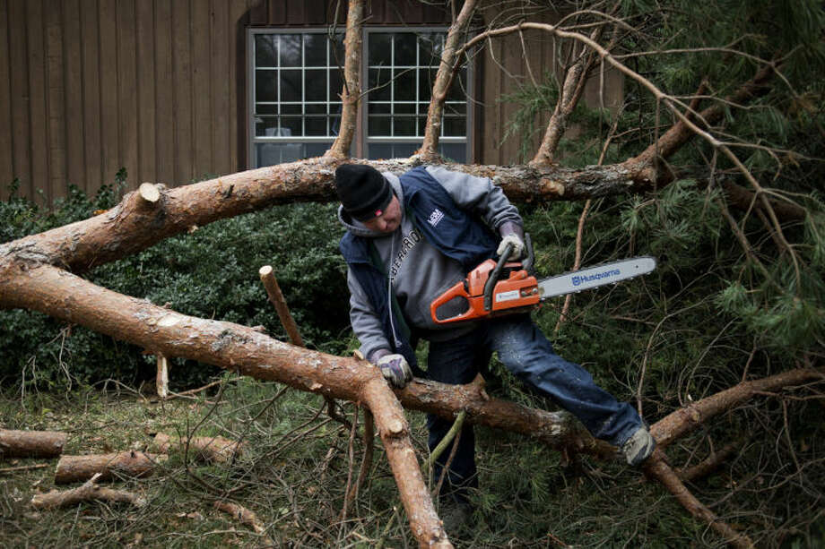 NEIL BLAKE | nblake@mdn.net Kim Krantz of Larkin Township works on removing a tree from his son-in-law's father's home on Camau Drive in Midland on Monday. Thousands in Midland remained without power as crews worked to clear the power lines and repair the damage done by Sunday's storm. Photo: Neil Blake/Midland  Daily News