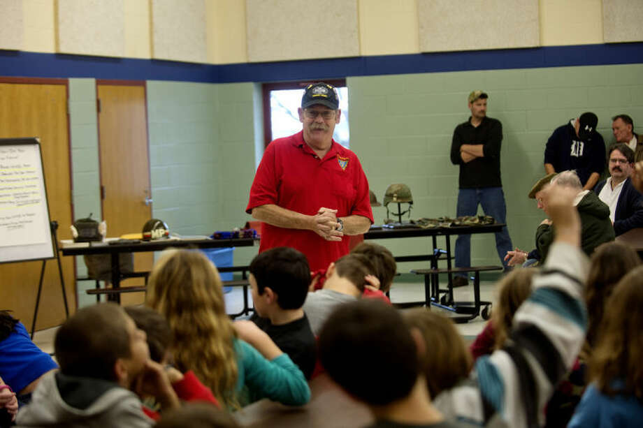 NICK KING | nking@mdn.netVietnam veteran Ray Essenmacher talks to the Auburn Elementary School fifth grade class during a Veterans Day event Monday in the school cafeteria. Essenmacher along with five other area veterans from various wars spoke to the class. Photo: Nick King/Midland  Daily News