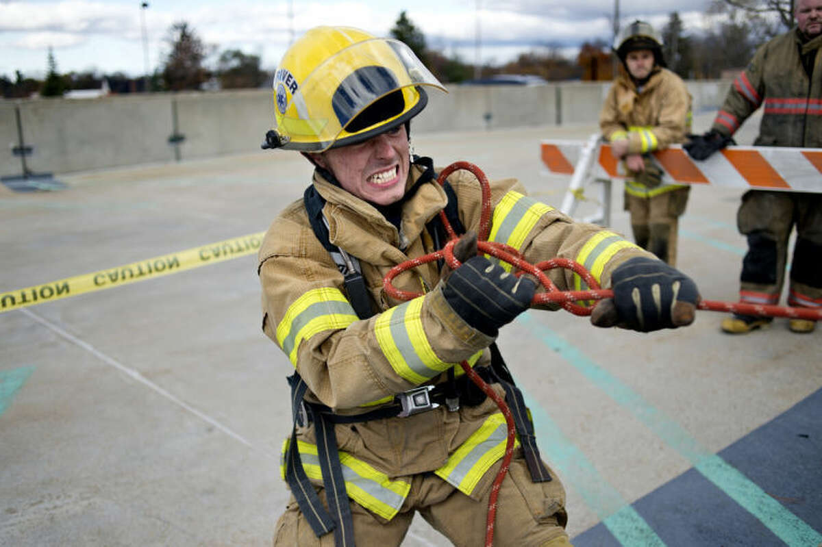 NEIL BLAKE   nblake@mdn.net Garrett Droelle of Midland hauls a hose to the roof of the Larkin Street parking ramp during the Midland Fire Department agility test on Friday. Applicants had to haul the hose up three stories with during a time limit.