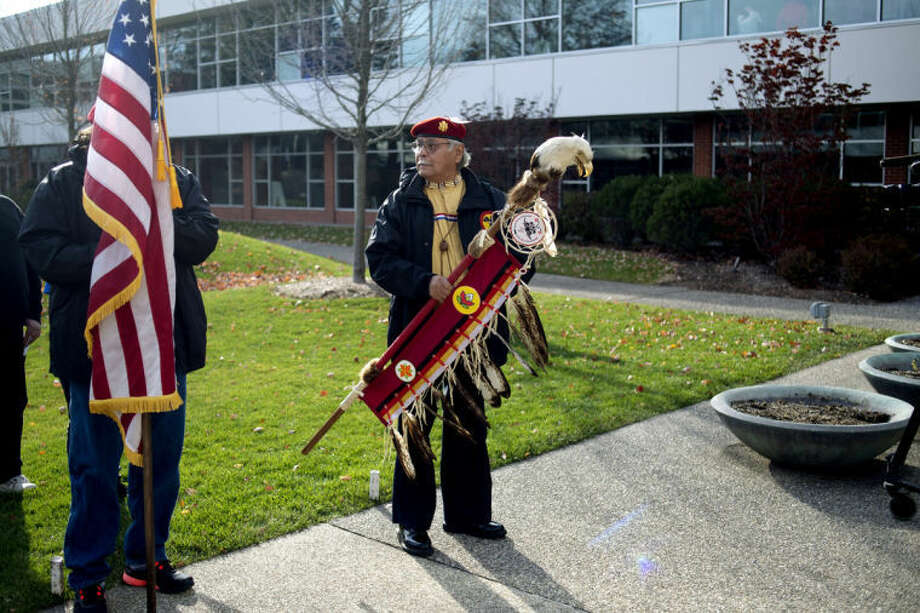 NEIL BLAKE | nblake@mdn.netAnishinabe Ogitchedaw Warrior Mike Perez carries the Eagle Staff as Kent Jackson holds the U.S. flag in the courtyard at Delta College on Thursday after conducting the Smudge Ceremony. The ceremony is used to ask for good feelings to come in and to drive away negative or feelings of doubt. Delta students participated in the ceremony before a talking circle took place to educate the students about Native American history. Photo: Neil Blake/Midland  Daily News