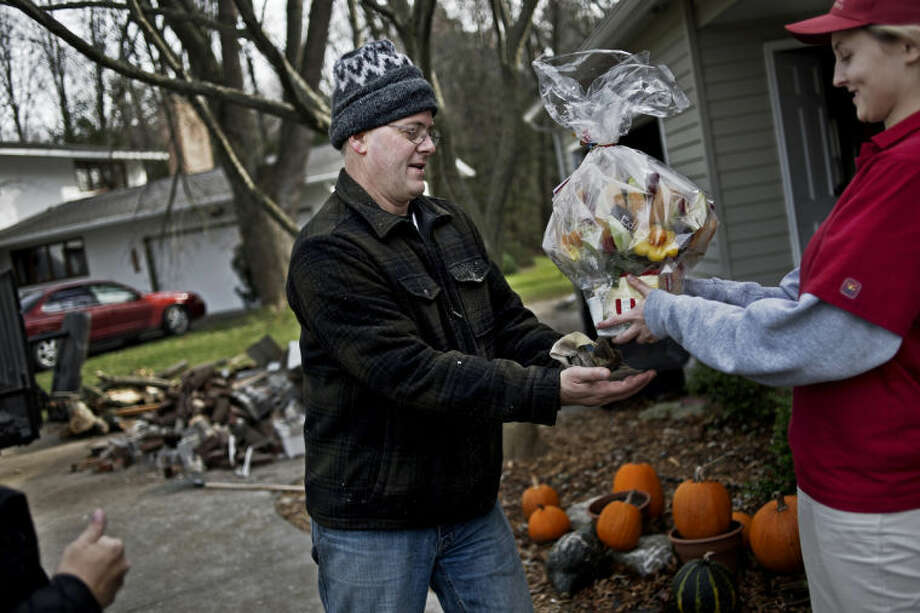 SEAN PROCTOR | sproctor@mdn.net Bruce Matthews, of Midland, accepts a fruit basket from Shelby Schafer, a Northwood sophomore, as Leigh Ochoa, of Birch Run, not pictured, looks on Wednesday afternoon outside of his house on Deerfield Court. After seeing the storm damage on Monday morning, Ochoa, who owns Edible Arrangements on North Saginaw, decided to donate baskets to residents whose houses and property suffered significant damage, visiting seven houses on Wednesday and planning to visit more on both Thursday and Friday. Matthews, who was working on clearing debris from his backyard, said he was leaf blowing when the storm hit, knocking trees over including some that hit his house. Photo: Sean Proctor/Midland  Daily News