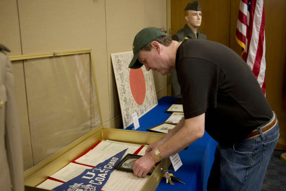 NEIL BLAKE | nblake@mdn.netMel Smith of Bay City arranges a display case for the Michigan Traveling Military Museum in the Alice and Jack Wirt Library in Bay City on Saturday. The museum is mostly made up of items that Smith has personally collected over the years. It is his goal to preserve the items and the stories of the people that once owned them. Photo: Neil Blake/Midland  Daily News